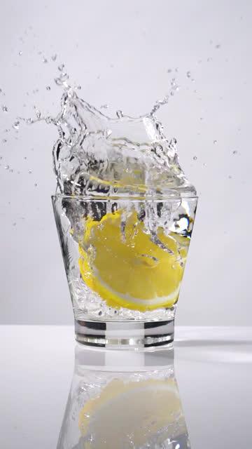 vidéos et rushes de tir vertical et ralenti de tranche de citron éclaboussant dans le verre - aliment en portion