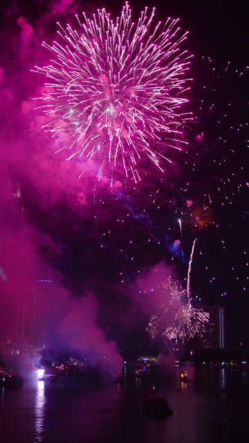 Vertical shot: New year fireworks at Chao Phraya River, Bangkok, Thailand.