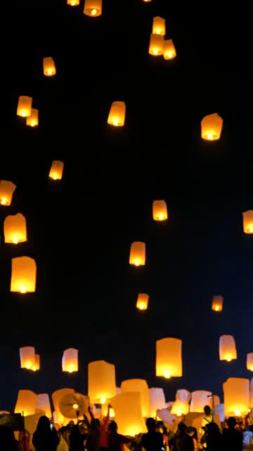 vertical shot of people releasing floating lantern during loi krathong or yee peng festival - vertical stock videos & royalty-free footage