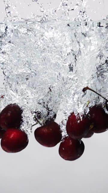vidéos et rushes de ralenti vertical : chute de cerise dans l'eau douce sur le fond blanc - baie eau