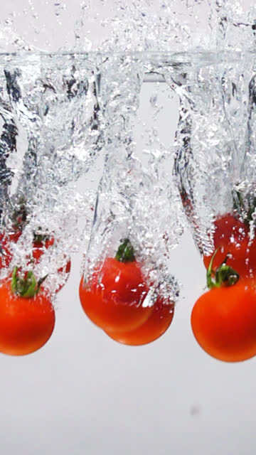 vertical slow motion: tomato drop into fresh water on white background - tomato stock videos & royalty-free footage