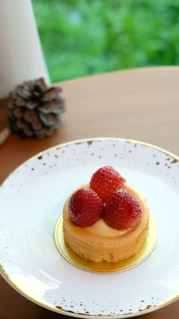 Vertical Strawberry cheese tart on a rotating plate