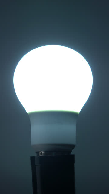 vertical: turn on and turn off a led light bulb - energy efficient lightbulb stock videos & royalty-free footage