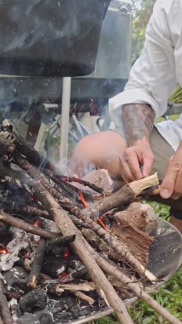 垂直視頻亞洲人手點燃營地火與木材 - 僅一成熟男士 個影片檔及 b 捲影像