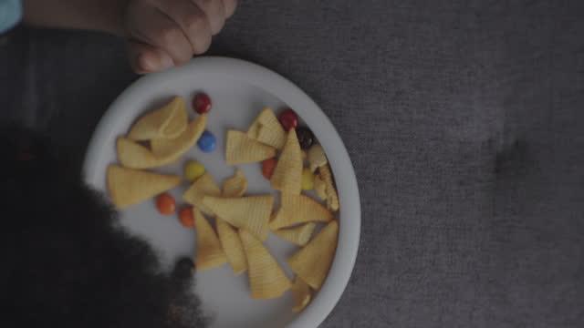 垂直ビデオ, 子供の肥満を引き起こす食べる - 男の赤ちゃん一人点の映像素材/bロール