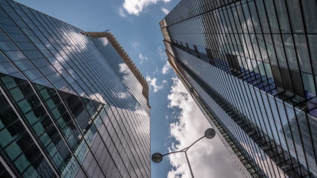 a vertical view looking up towards new skyscrapers under construction in the city of london with blue skies and rapidly moving clouds reflecting in the buildings glass facades - city of london stock videos & royalty-free footage