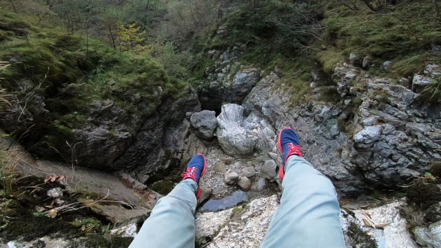 vertigo view of a guy sitting on the edge of dry waterfall. - 高い点の映像素材/bロール