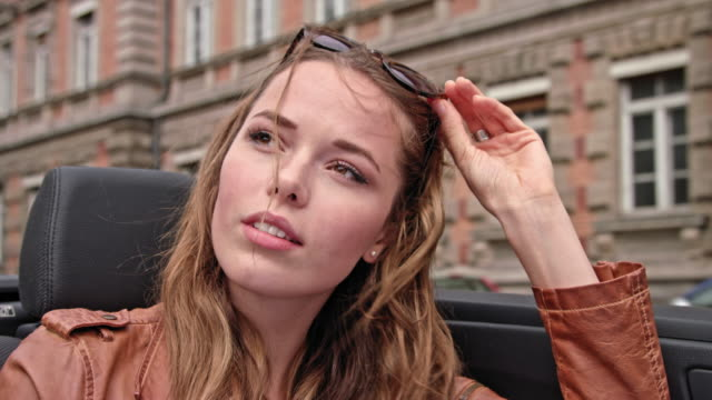 vidéos et rushes de very attractive woman sit's in the back of a convertible car while driving on a road with old buildings - voiture décapotable