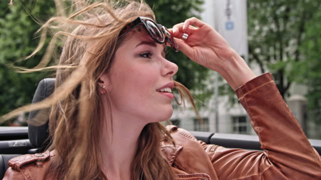 very attractive woman sit's in the back of a convertible car while driving on a Munich city road