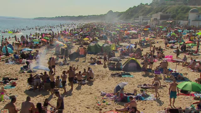 very crowded bournemouth beach in the heatwave during coronavirus lockdown crowds make it hard for social distancing to be observed - bournemouth stock-videos und b-roll-filmmaterial
