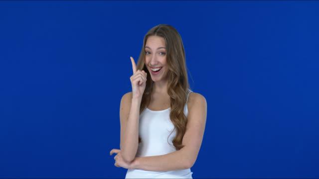 非常にかわいいとかわいい女の子は笑顔と手で警告サインを示しています. - 気を惹く点の映像素材/bロール