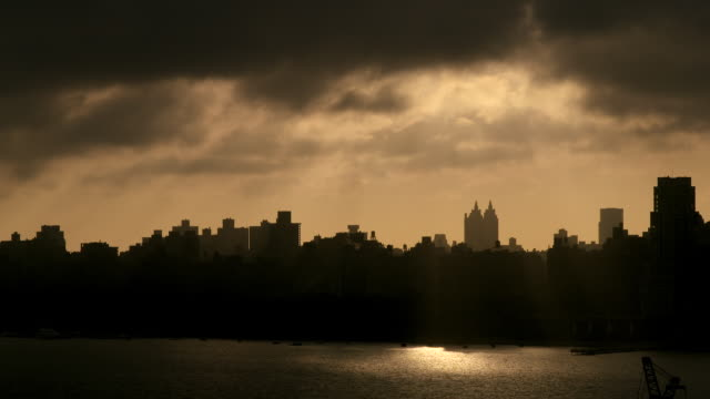 Very dramatic dark and gloomy morning on the Manhattan Skyline.  The sun is reflecting on the water and the city is in dark silhouette.  The clouds are very ominous and dark but the sun is breaking though.