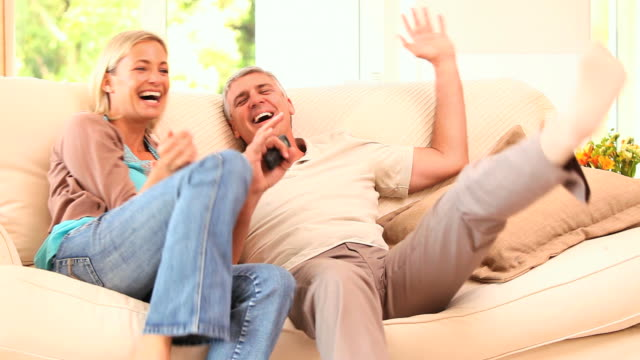 Very happy couple watching sports on tv / Cape Town, Western Cape, South Africa