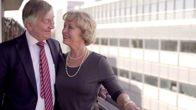 very happy retired couple on a city balcony. - skjorta och slips bildbanksvideor och videomaterial från bakom kulisserna