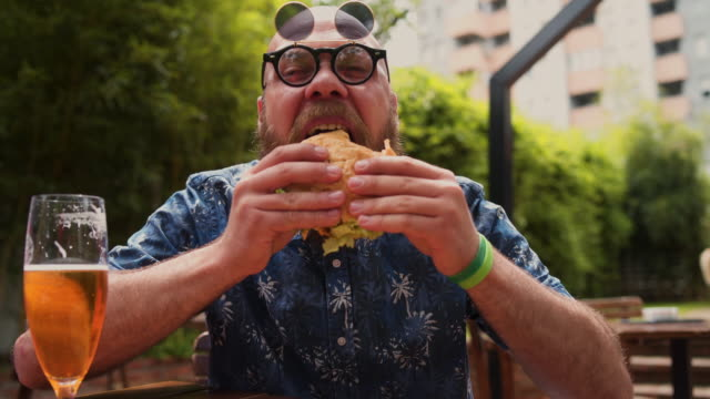 very hungry man biting his burger - moustache stock videos & royalty-free footage