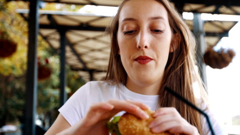 very hungry woman biting her burger - enjoyment stock videos & royalty-free footage