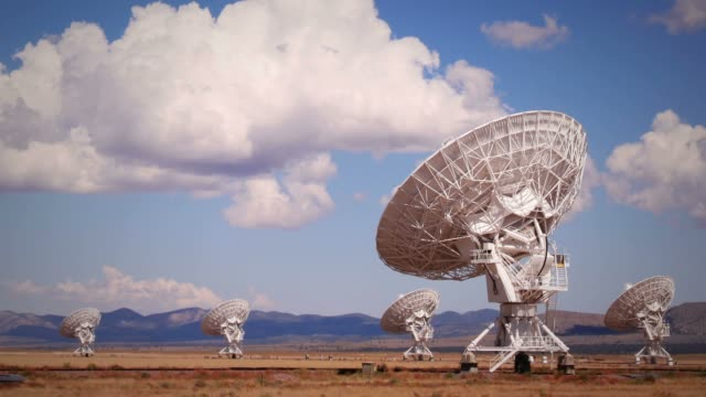 very large array telescopes swivel in unison beneath billowing clouds. - 天体望遠鏡点の映像素材/bロール