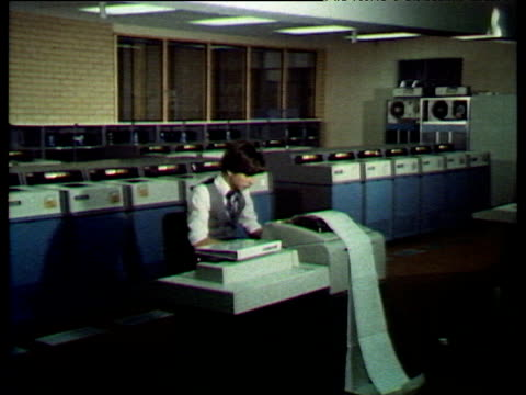 very large dated computers and printers people working at them; 1980s - början bildbanksvideor och videomaterial från bakom kulisserna