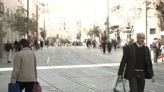 very modern tram drives through the old city in jerusalem. nine israelis have been killed in a series of stabbings, shootings and hit-and-run attacks... - 路面軌道点の映像素材/bロール