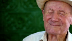 Very old man portrait with emotions. Grandfather happy and smiling. Portrait: aged, elderly senior. Close-up of a pensive old man in white hat sitting alone outdoors at summer. Slow motion