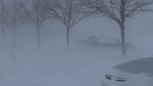 Very powerful winds rip through a parking lot creating whiteout conditions as vehicles disappear behind a wall of snow during an intense blizzard in...