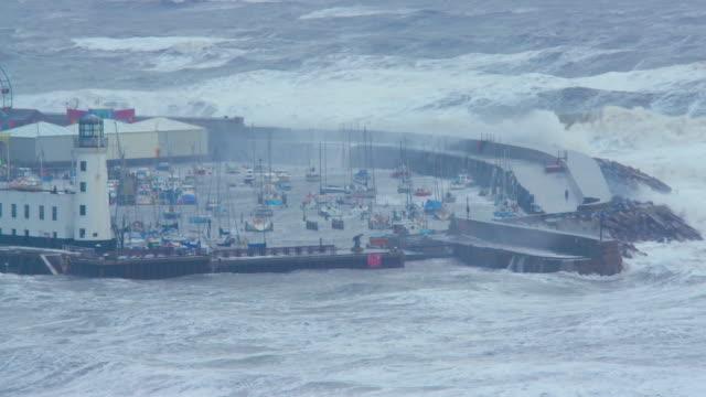 vídeos de stock, filmes e b-roll de very rough north sea  lighthouse & harbour, scarborough, north yorkshire, england - scarborough norte de yorkshire