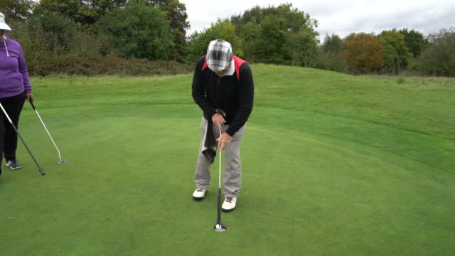 a very short putt and picking the ball up with the handle of the putter. - sun visor stock videos and b-roll footage