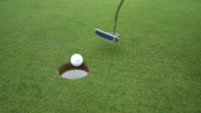 A very short putt into the hole.