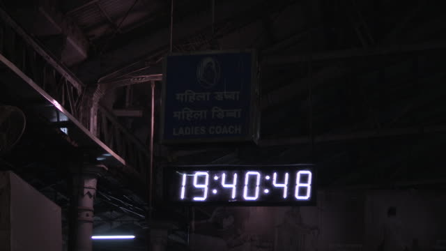 Very slow tilt up over a digital clock showing the time twenty to seven in the evening under a sign indicating the position of the ladies' coach on a...