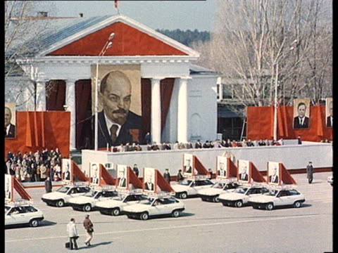 Very solemn communist parade w/ white cars topped by portraits of leaders of the CPSU Communist Party huge portrait of Lenin in BG