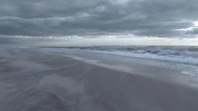 Very strong gale force winds blow sand towards the ocean at Jones Beach New York on a cold winter day