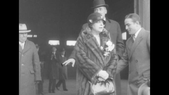vídeos de stock, filmes e b-roll de very tall man with a mustache and bowler hat walks to camera woman wearing fur coat accompanies him man gestures for them to pose for photos they do... - alto descrição geral