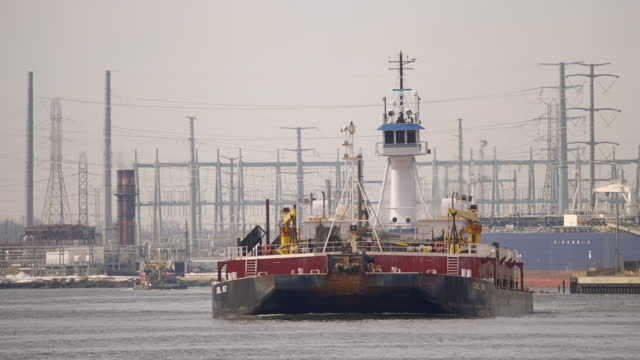 very tall tugboat pushing a barge in in an industrial setting - trade union stock videos & royalty-free footage