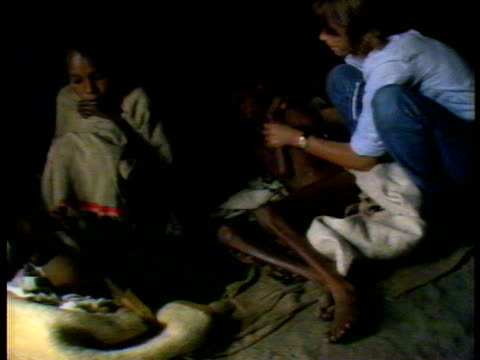 very thin famine victim being examined by western nurse another child wrapped in blanket on left ethiopian famine jul 84 - ausgemergelt stock-videos und b-roll-filmmaterial