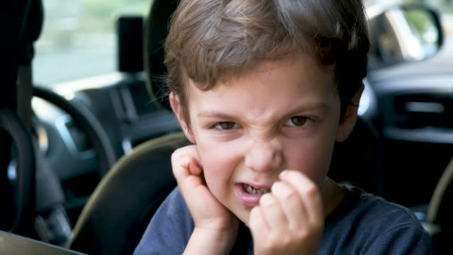 very upset frustrated little boy looking through a car window, he does not want to go back to school - displeased stock videos & royalty-free footage