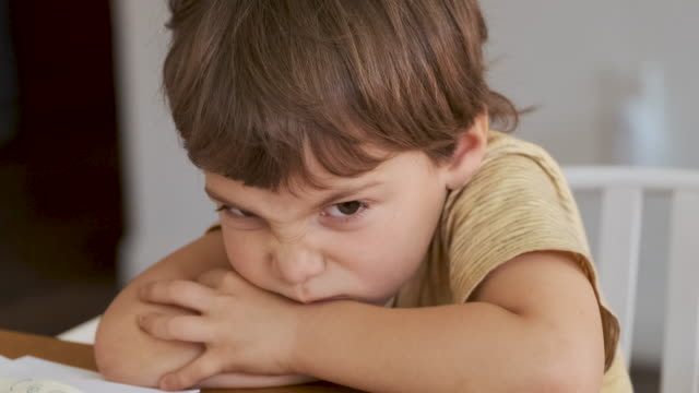 vidéos et rushes de très contrarié petit garçon frustré assis à sa cuisine à la maison, il ne veut pas retourner à l'école - grognon