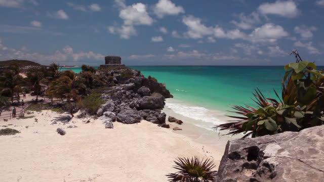 very wide, static shot of waves washing ashore with a small ancient building on a cliff. - cancun stock videos & royalty-free footage