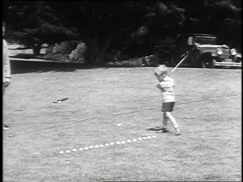 vídeos de stock, filmes e b-roll de 1930 ha very young boy hitting a line of golf balls on ground, one after the other, without missing any, june 8, 1930 / san fransisco, california  - golfe