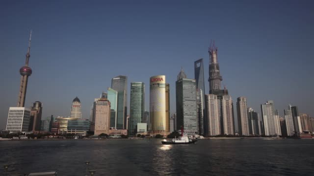 A vessel sails past commercial buildings in the Pudong area seen from the Bund in Shanghai Bund waterfront in Shanghai on January 28 2013 in Shanghai...