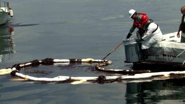 stockvideo's en b-roll-footage met vessels of opportunity chartered by bp skim for oil off the coast of pensacola / they use a 'horseshoe' boom / fishermen try to skim oil caught up in... - 2010