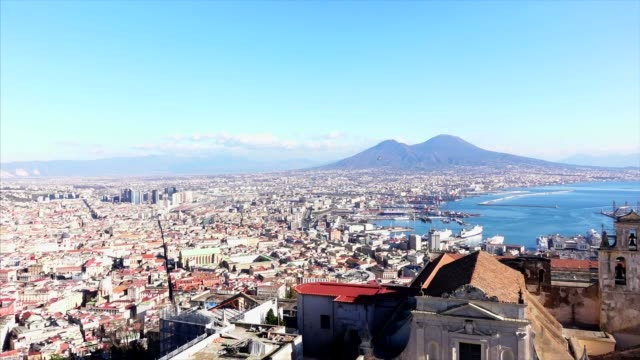 Vesuvio and Naples waterfront with rocks and boats