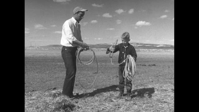 us veteran dale sprout and his young son stand outdoors on their homestead each holding a coil of rope son makes learner's attempt at lassoing / note... - young war veteran stock videos & royalty-free footage