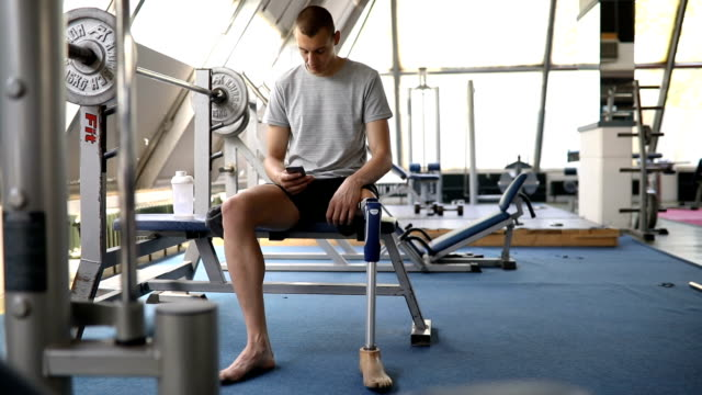 veteran texting in the gym on a bench press - amputee stock videos & royalty-free footage