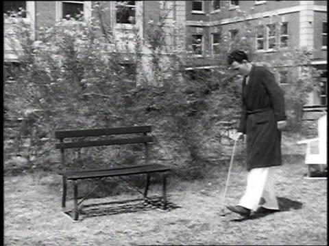 vidéos et rushes de veteran walking to bench with cane / veteran sits on bench - banc