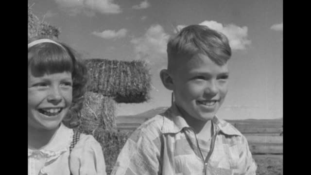 usaf veteran/homesteader dale sprout and his young son practice roping calves as two children perched on stack of hay bales look on / very qs dale's... - young war veteran stock videos & royalty-free footage