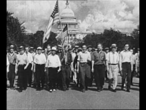 veterans' bonus army marchers approach, pass camera; man in military uniform at head of procession carries us flag; us capitol stands in background /... - military uniform stock videos & royalty-free footage