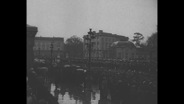 Veterans march down street crowds on either side / veterans holding flags march towards camera / King Leopold watches from porch of building as...