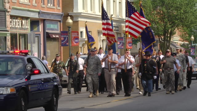 ms slo mo veterans of united state armed forces march in memorial day parade down at main street of mid-western town / chelsea, michigan, united states   - veteran stock-videos und b-roll-filmmaterial