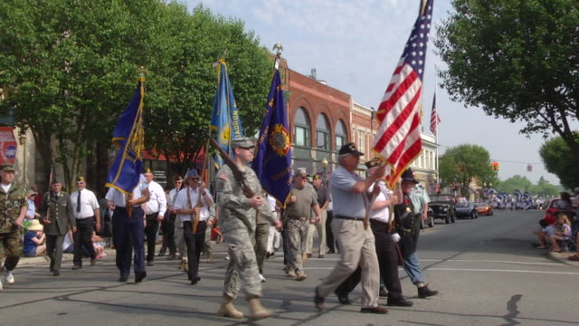 vidéos et rushes de ms ts slo mo veterans of united state armed forces march in memorial day parade down at main street of mid-western town / chelsea, michigan, united states   - armée américaine