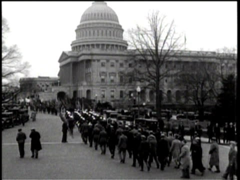 veterans with flags marching down the street while spectators watch from the sidewalk near some parked cars / veterans marching toward the capitol /... - anno 1932 video stock e b–roll